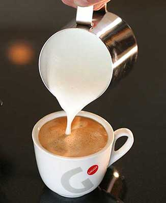 An image of steamed milk poured into a cup of espresso